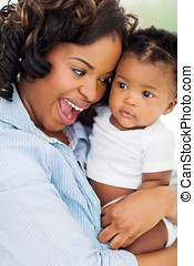 happy african American woman holding baby girl