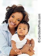 young african American mother holding baby girl - cheerful...
