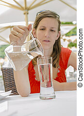Young woman pouring water into a glass