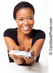 young black woman presenting south african money
