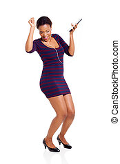 african woman dancing with a tablet computer