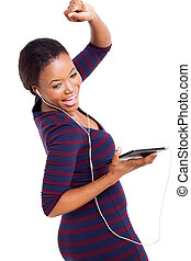 african woman dancing with tablet computer - cheerful...