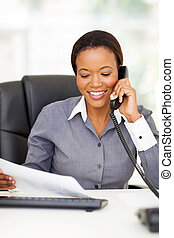 african american office worker talking on landline phone -...