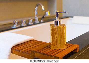 Liquid soap bottle on the bathtub in modern bathroom