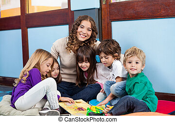 Teacher Sitting With Children On Floor - Happy teacher...