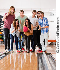 Woman Bowling While Friends Cheering - Young woman bowling...