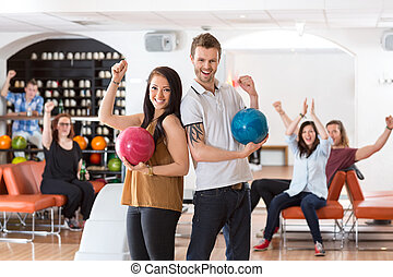 Excited Man And Woman With Bowling Balls in Club - Portrait...