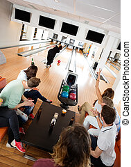 Friends Cheering Woman Bowling in Club - High angle view of...