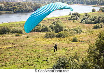 Landing - Parachutist sits down on a meadow near the river