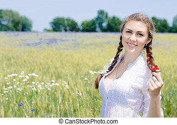 Young beautiful woman walking in green wheet field on summer...