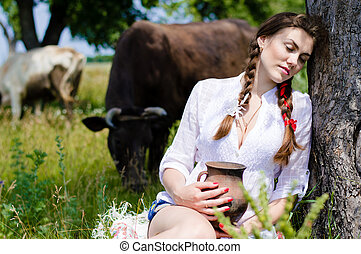 Young woman sitting tired near cows in countryside