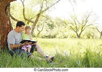young father with his little daughter reads the Bible - a...