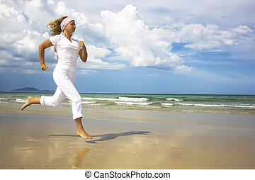 Healthy life - Young woman is running near the ocean. Space...