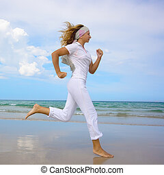 Woman running - Young woman running near the ocean Space for...