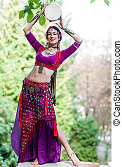 Oriental Dancer with tambourine in the park