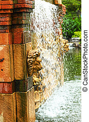 Waterfall in the garden - a lions head statue