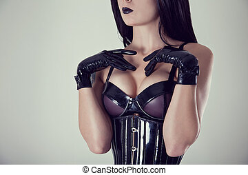 Close-up shot of female breasts in latex bra, studio shot