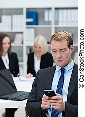 Businessman reading a text message on his mobile phone while...