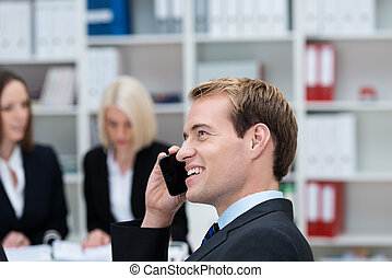 Happy businessman chatting on his mobile phone at the office...