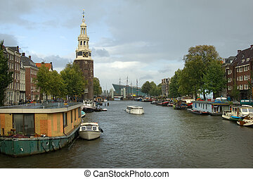 Amsterdam cityscape - Houseboats and merchant houses along...