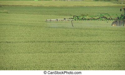 Tractor spraying on field