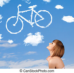 Young girl looking at bicycle clouds on blue sky - Young...