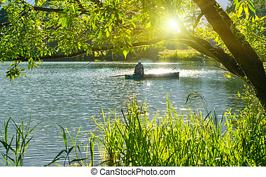 Inveterate fisherman in a boat on the lake Summer fishing