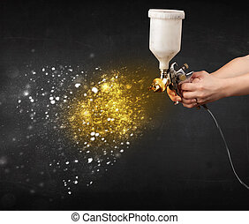 Worker with airbrush painting with glowing golden paint and...