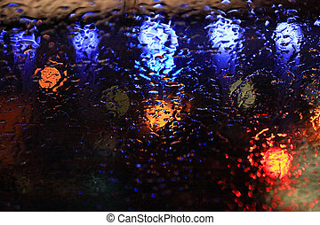 Raindrops on the glass over defocused street lights in the...