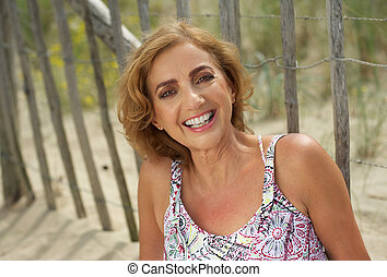 Attractive middle aged woman smiling outdoors - Closeup...