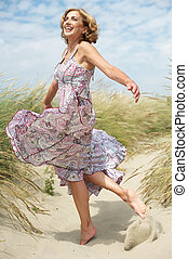 Beautiful middle aged woman dancing outdoors - Carefree...