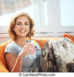 Attractive older female drinking outdoors - Closeup portrait...