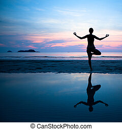 Woman practicing yoga on the beach after sunset.