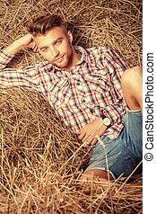 haystack - Handsome young man lying in haystack.