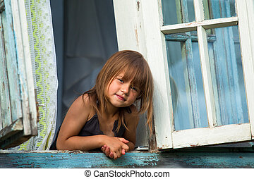 Little girl looks out the window rural house