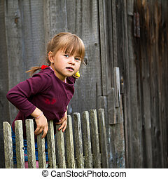 Little five-year girl and vintage rural fence (square)