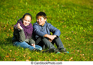 Teenage couple sit in autumn park