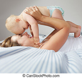 Portrait of happy young mother hugging cute baby - Closeup...