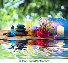 two candles and towels black stones and purple flower on...