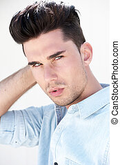Attractive male fashion model with hand in hair