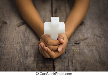 Holding a Religious Cross - A person holding a white...