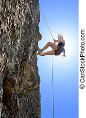 Woman Climbing Rock - Full length of young woman climbing...