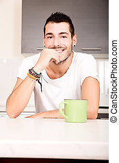 Coffee Time - A young man sitting in the kitchen and...