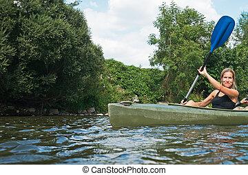 Women kayaking - Two smiling young women kayaking down a...