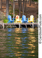 Lakeside seats - Colourful Muskoka chairs sit on the cottage...