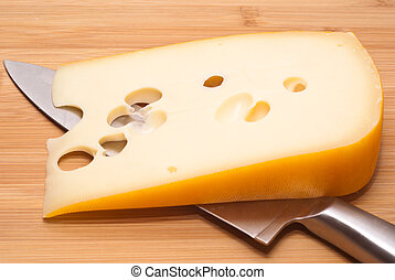 Swiss cheese emmenthal and knife on wooden board