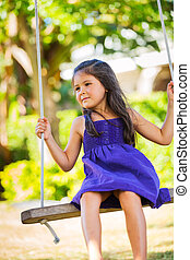Girl Playing on Swing Set - Cute Little Girl Playing on...
