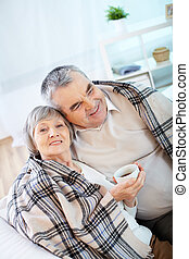 Resting at home - Portrait of a happy senior couple wrapped...