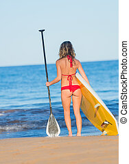 Attractive Woman with Stand Up Paddle Board, SUP, on the...