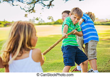 Kids playing Tug of War - Group of Happy Young Children...
